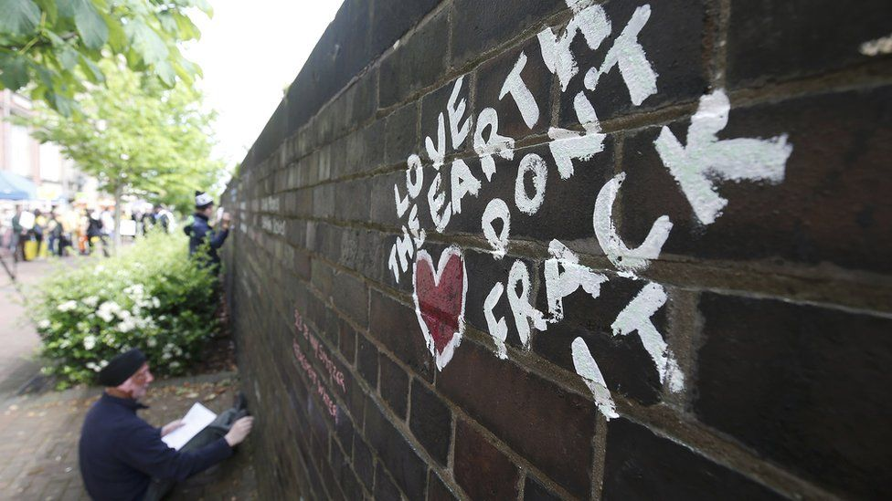 An anti-fracking protester writes messages on a wall in Lancashire