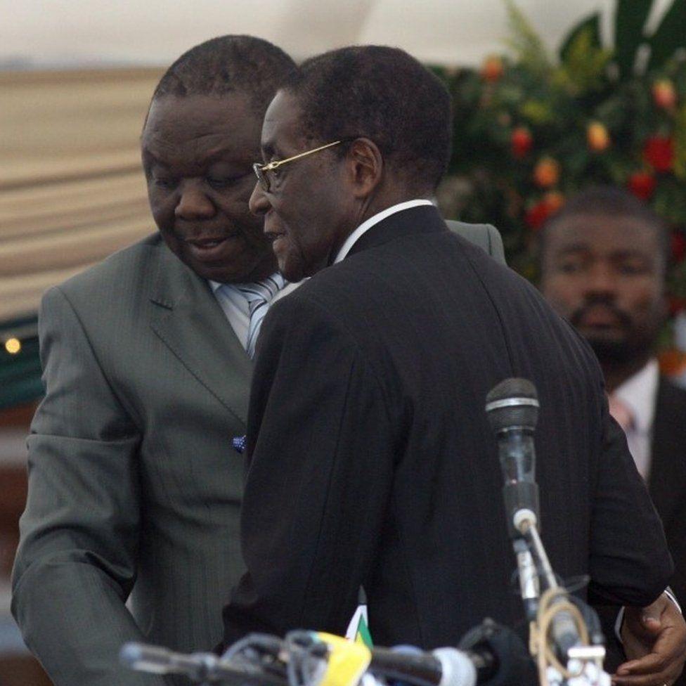 Morgan Tsvangirai leaves after being sworn in by President Robert Mugabe
