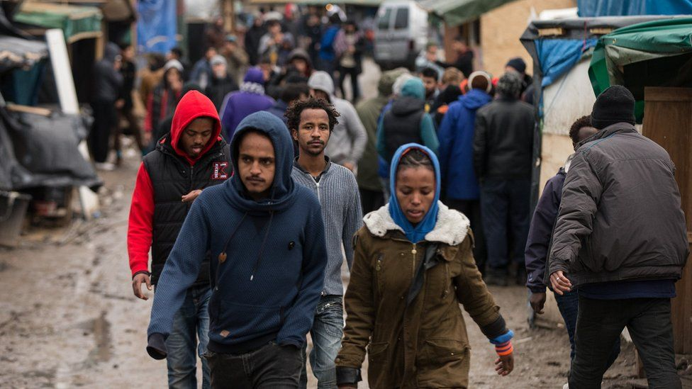 "Migrants walk through the camp known as ""The Jungle"" in Calais"