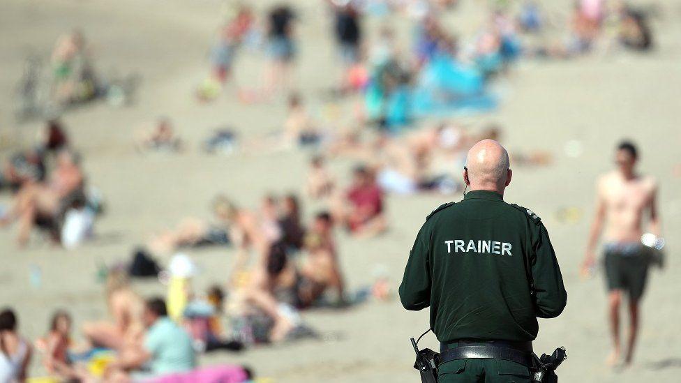 A PSNI officer views the crowd enjoying the Sunday sunshine at Ballyholme beach, Bangor, Co Down