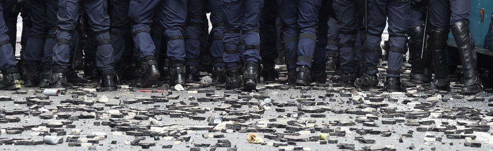 French anti-riot police officers stand as stones and rubbish lie on the pavement during a demonstration against proposed labour reforms near the Hospital Necker in Paris on 14 June 2016