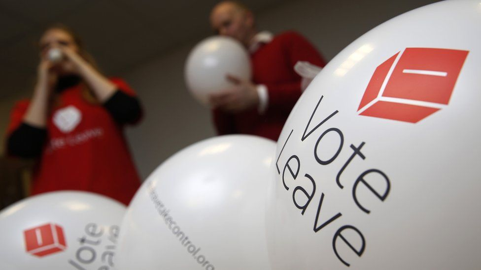 Campaign workers blow up balloons advertising the Vote Leave campaign