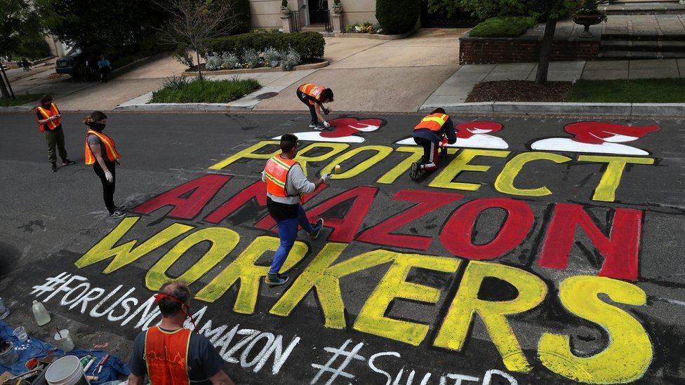 """Several people contribute to paining a very large """"protect Amazon workers"""" sign on the road outside a very affluent home"""