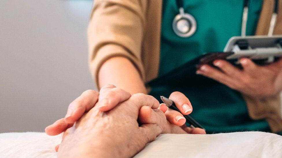 file picture of doctor holding patient's hand