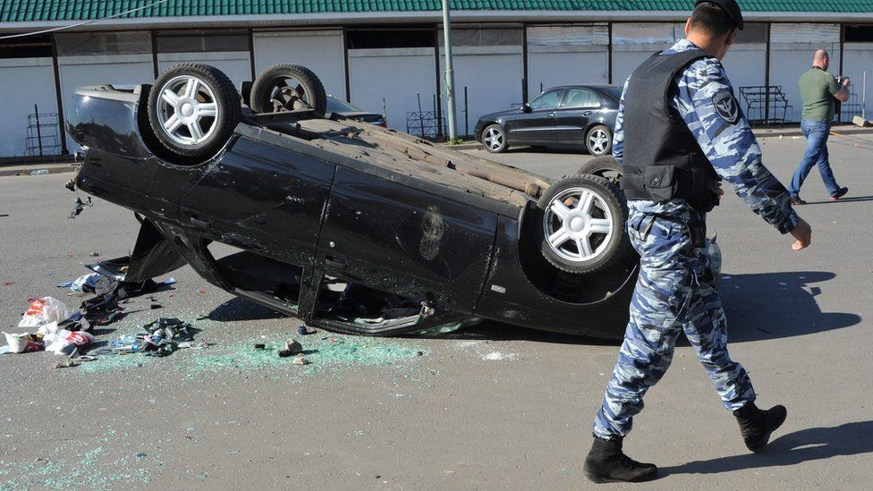 Russian riot policeman passes by an overturned car after a mass brawl at the Khovanskoye cemetery in Moscow, Russia, 14 May 2016.