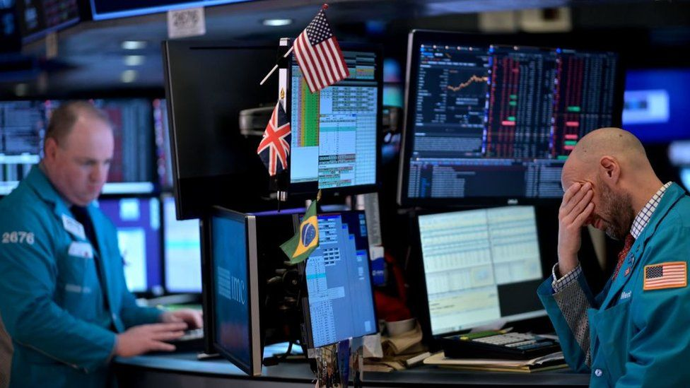 Trader with his head in his hand at the New York Stock Exchange