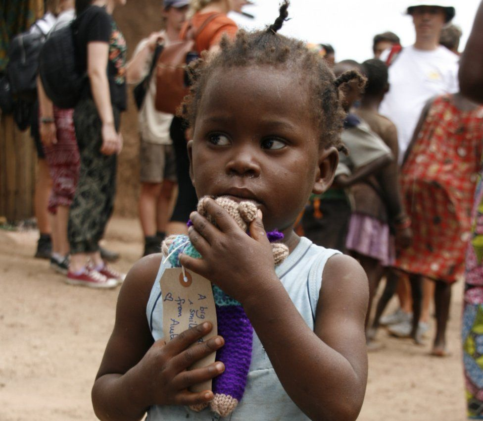 Child in Africa with knitted teddy