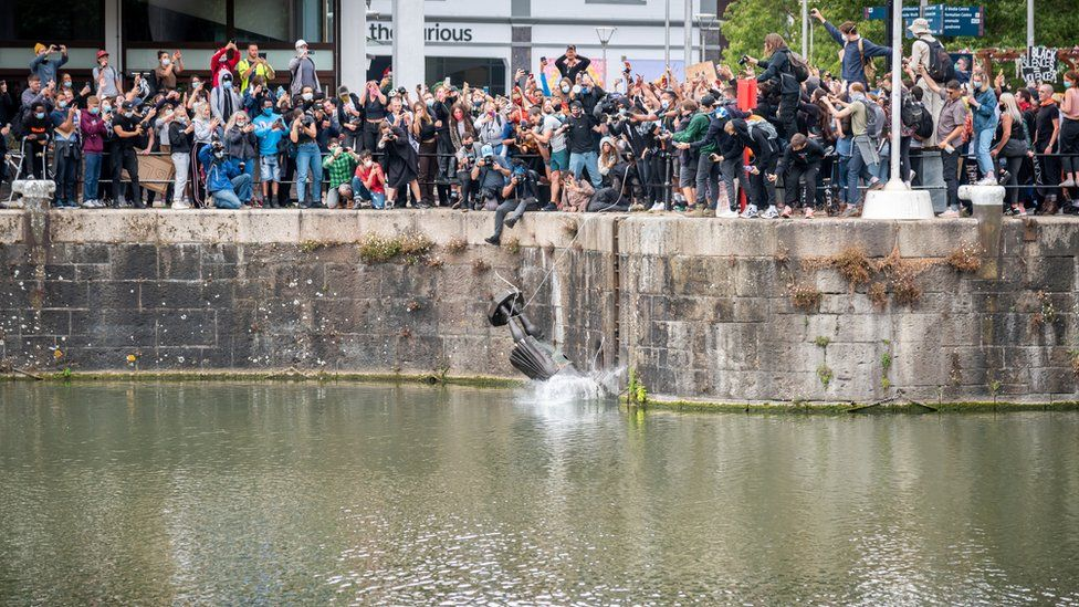The statue of Edward Colston falls into the water after protesters pulled it down and pushed into the docks,