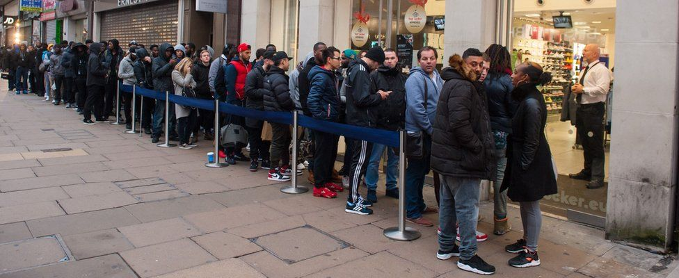 """Shoppers queue outside a branch of Foot Locker on Oxford Street, London, as many retailers offer one day sales for """"Black Friday"""" in 2014"""