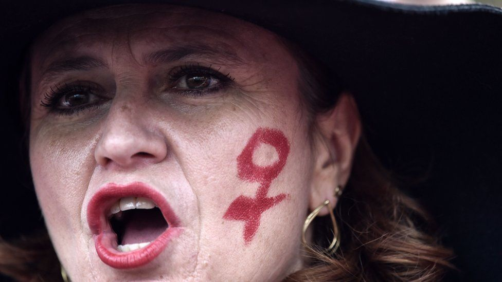 A woman with the female gender symbol on her cheek takes part in a march as part of the International Day for the Elimination of Violence against Women, on November 24, 2018 in Rome