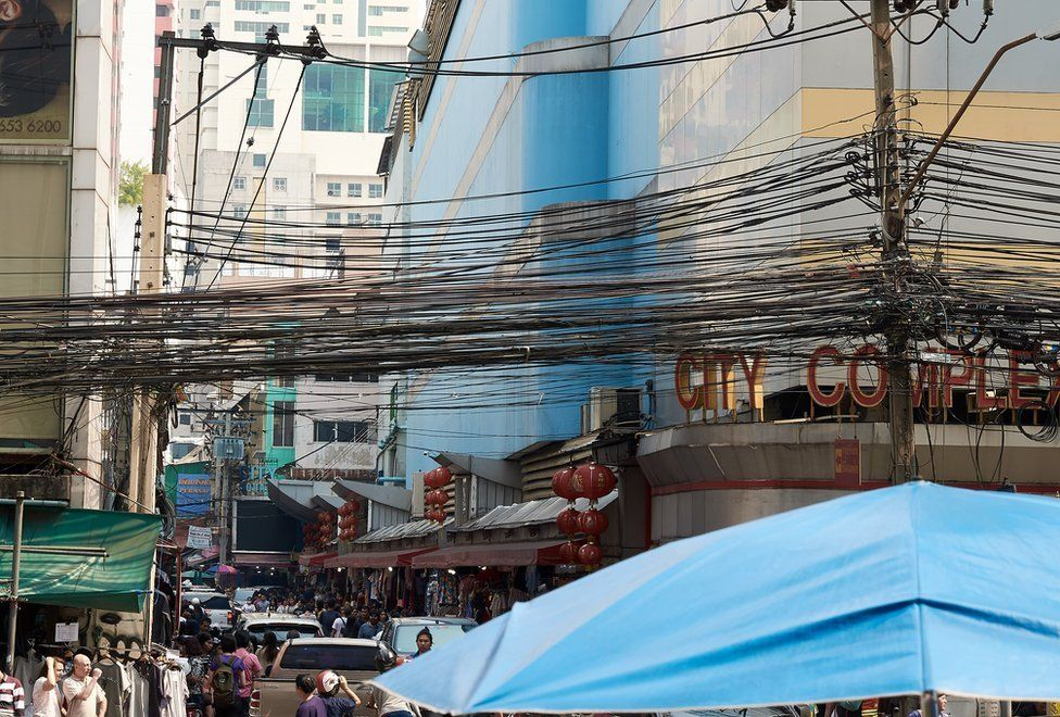A mass of communication and power cables strung above the street keeping the city connected