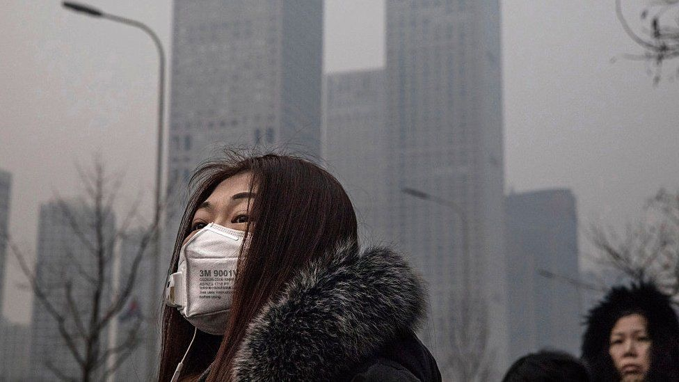 Woman wears mask due to pollution in Beijing. 12 Dec 2016
