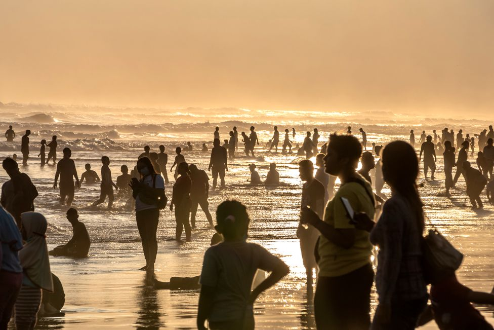 People stand in the ocean surf as the sun sets