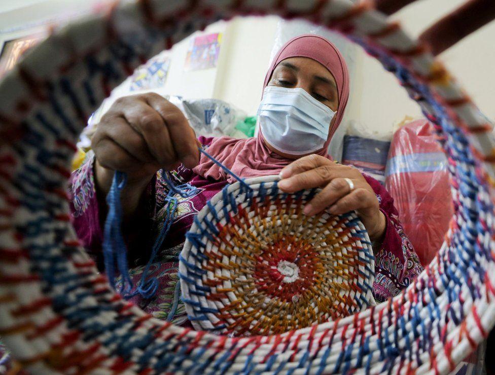 A woman knits a multi-coloured basket.