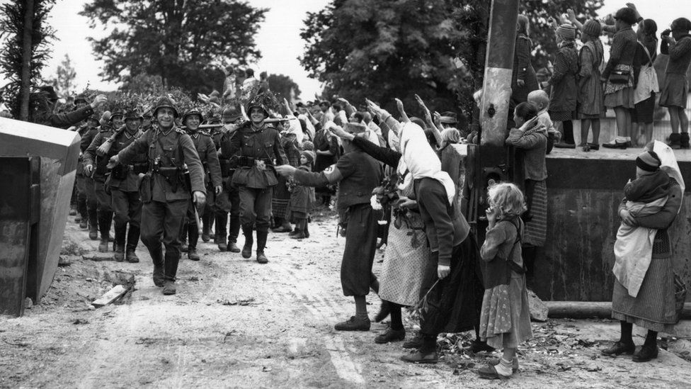 Wehrmacht soldiers entering Czechoslovakia in 1938 as locals salute