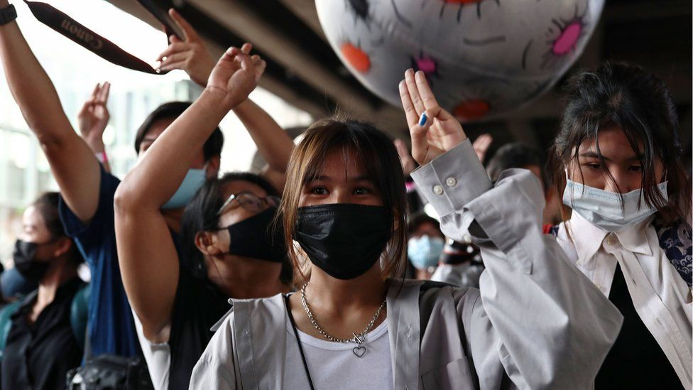 Protesters hold up the three-finger salute during a rally in Bangkok, 21 November 2020