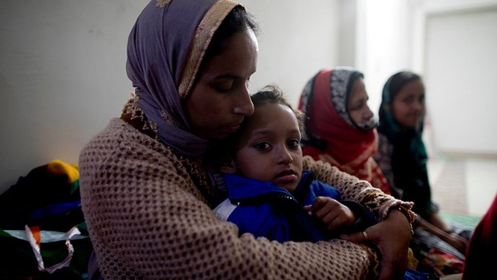 A woman holds her daughter at Al-hind Hospital where they have taken shelter with other families after losing their homes following sectarian riots over India's new citizenship law, in Delhi, 28 February