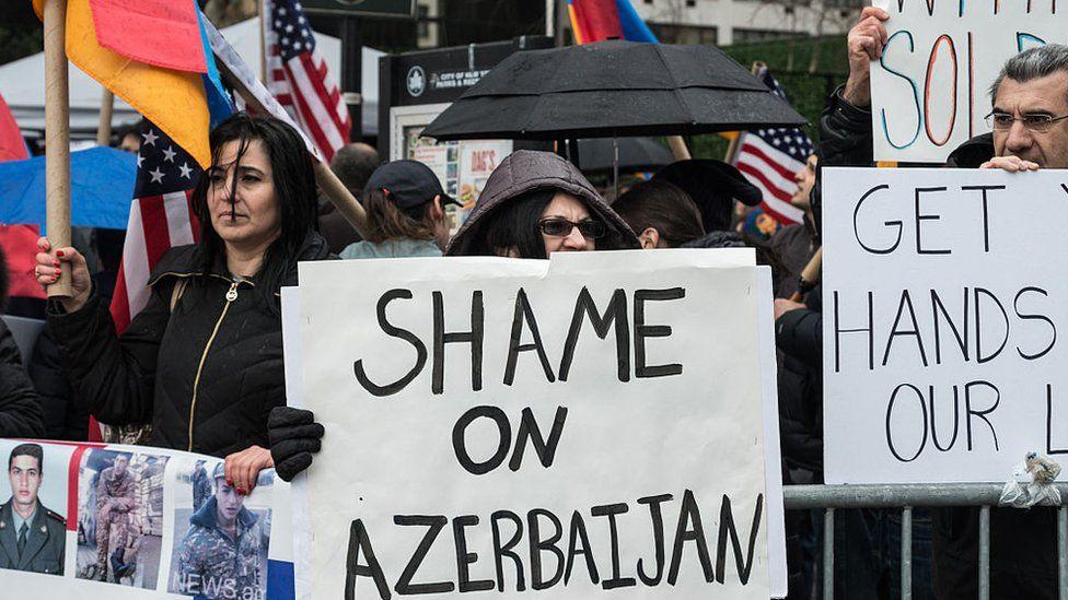 Armenian protesters hold a sign saying Shame on Azerbaijan