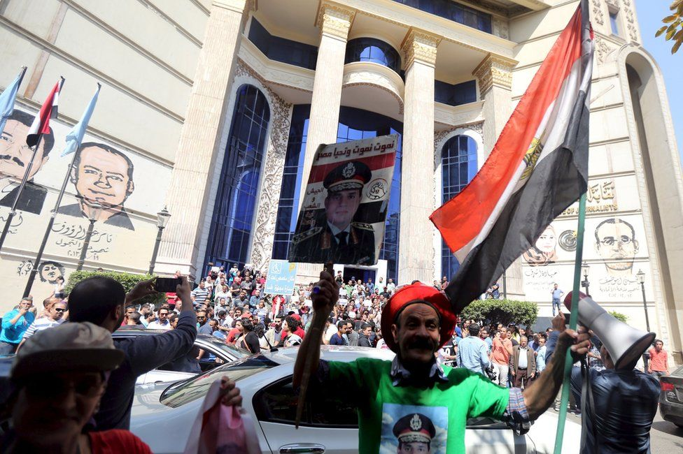 Supporter of President Abdul Fattah al-Sisi stands in front of anti-government protesters, outside the Egyptian journalists' union building in Cairo (15 April 2016)