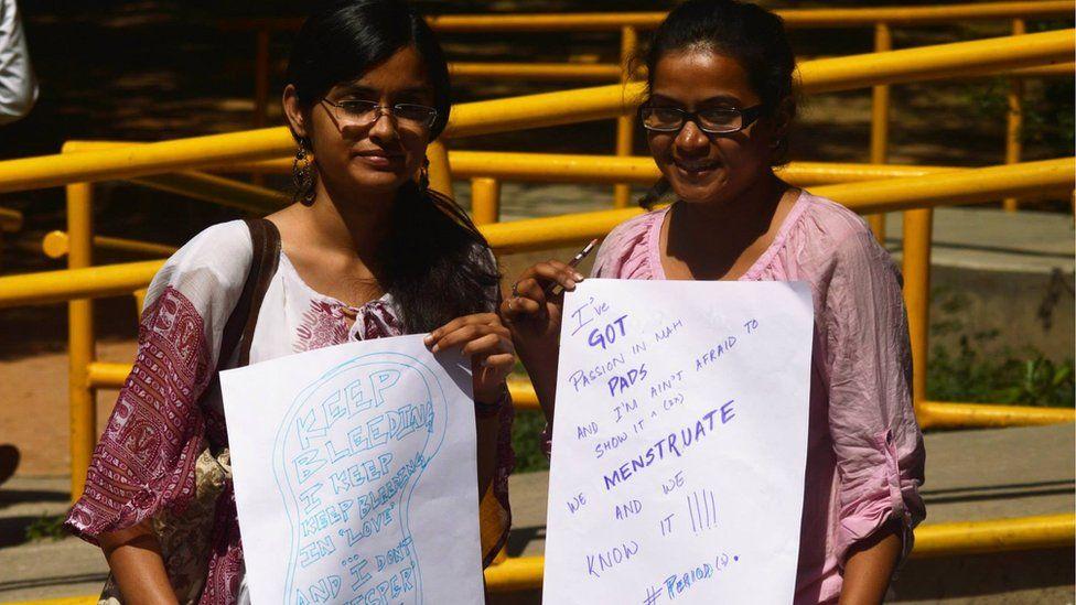Women holding #HappyToBleed posters