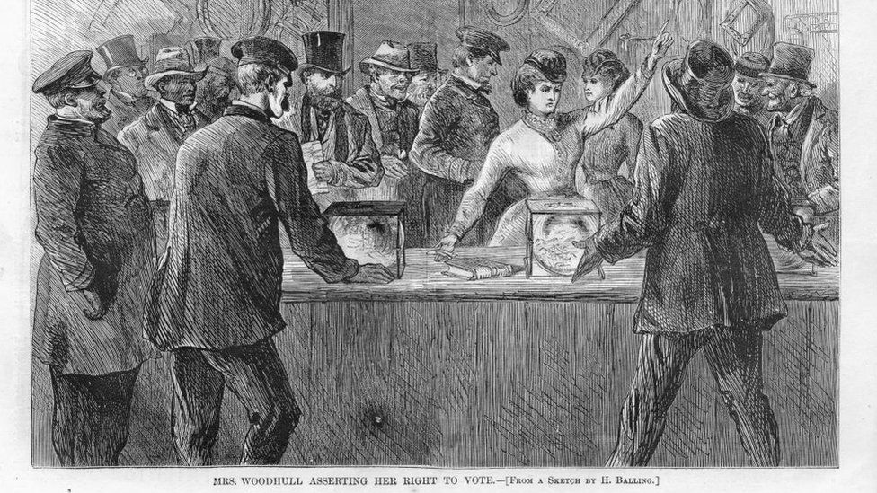 "Black and white print illustrating Victoria Woodhull, the first woman candidate for President, with her arm raised, after breaking into a polling station and demanding to be allowed to vote, titled ""Mrs Woodhull Asserting her Right to Vote, "" illustrated by H Balling for the American market, 1871"