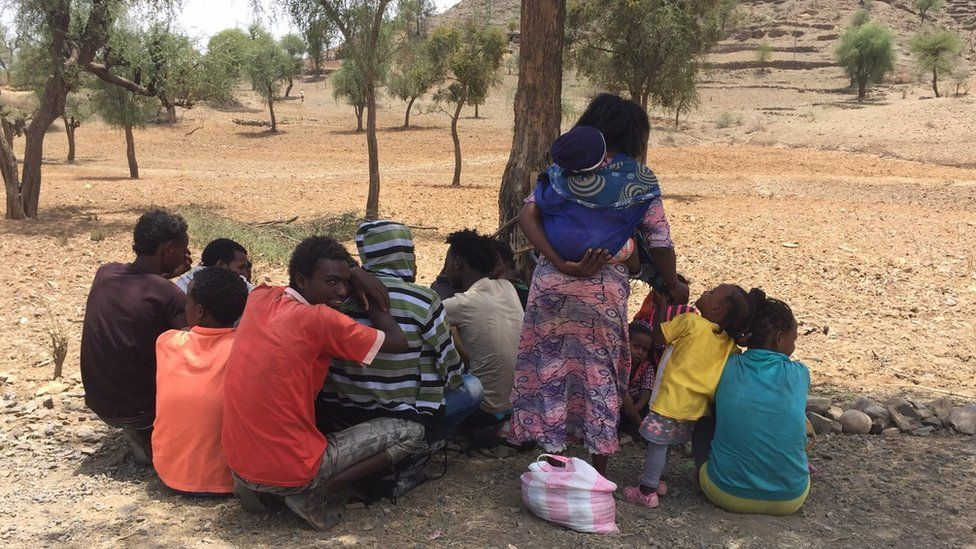 Eritrean refugees sitting under the shade of a tree in Ethiopia