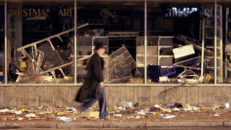 "A picture taken 28 April 2007 shows a man passing by a destroyed shop after two days of riot in the center of Tallinn, after Estonian authorities took measures to remove the ""Monument to the Liberators of Tallinn"" - an homage"