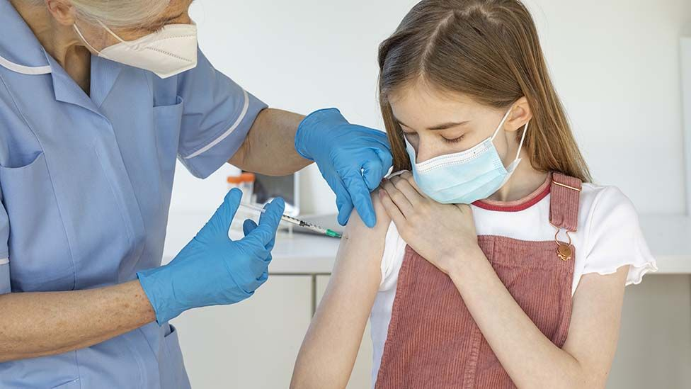 Girl being vaccinated by nurse