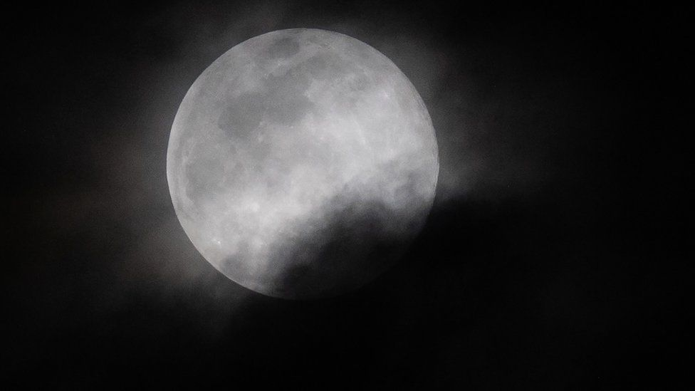 The super worm moon partly covered in cloud
