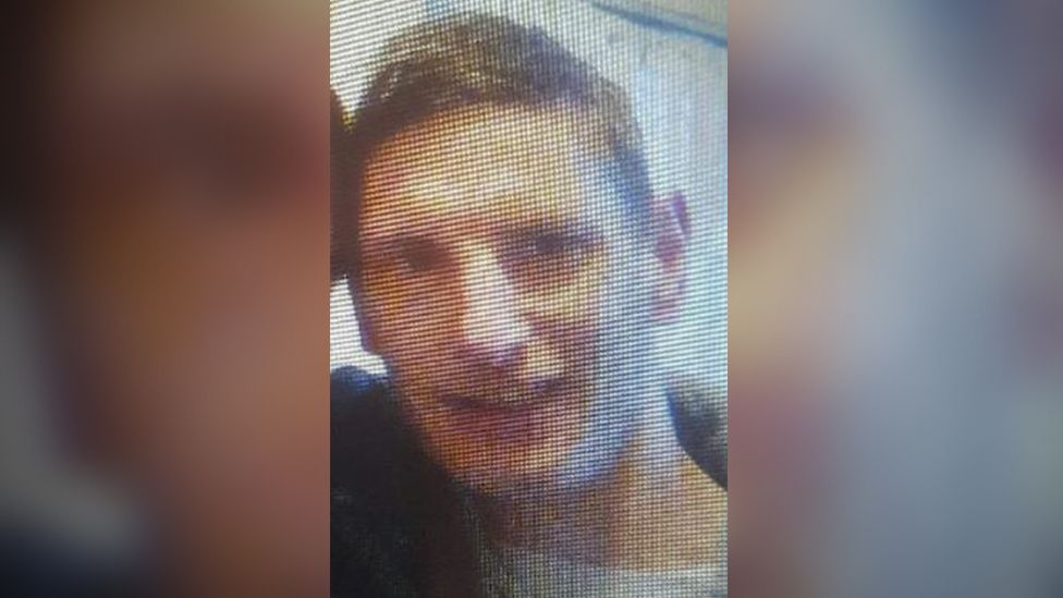 A photo of Damian John Hill. It looks to be a photo of a photo on a screen. He has short brown hair and is smiling i the image.