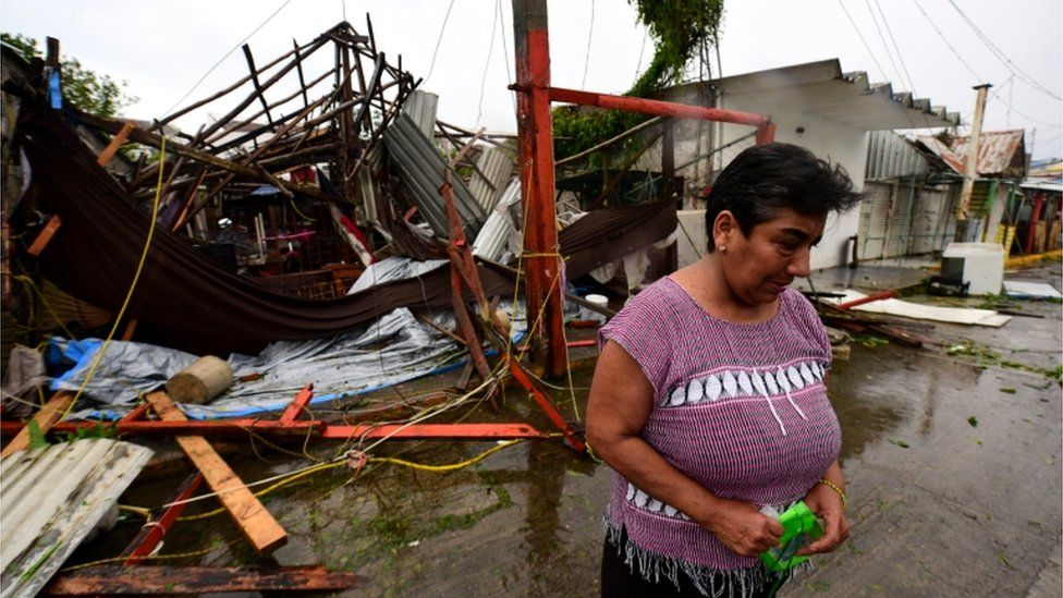 Martha Sanchez reacts while walking in front of her souvenir store that was destroyed when Hurricane Grace slammed into the coast with torrential rains, in Costa Esmeralda, near Tecolutla, Mexico, 21 August 2021