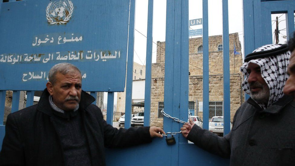 Palestinian men symbolically lock shut the gates of an Unrwa office in the West Bank city of Hebron on 17 January 2018