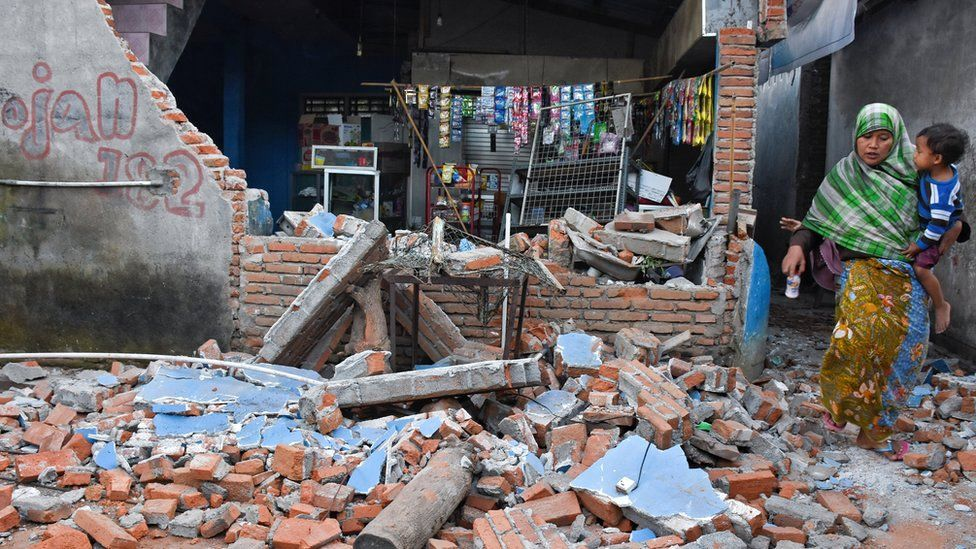 A woman walks past debris from a collapsed wall following a strong earthquake in Lendang Bajur Hamlet, Lombok island,