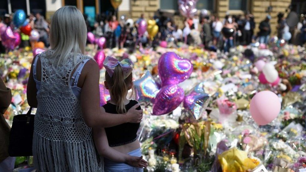 """People gather to see flowers and messages of support in St Ann""""s Square in Manchester, northwest England on May 25, 2017"""