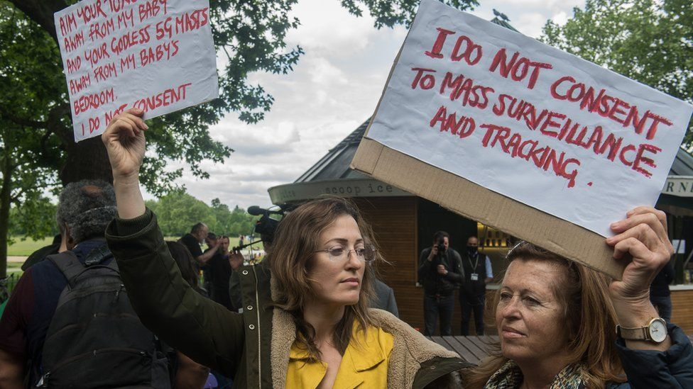 Two women hold signs at an anti-lockdown protest