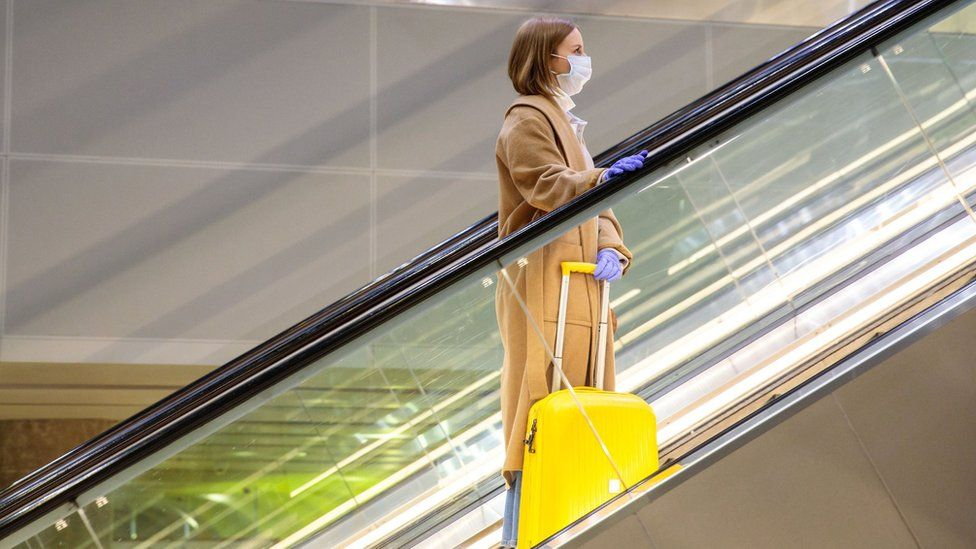 Woman on escalator in airport with luggage.