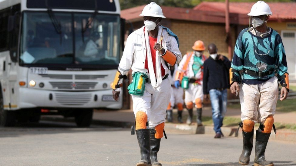 Mine workers wearing face masks arrive at a mine in Carletonville, South Africa, 19 May 2020
