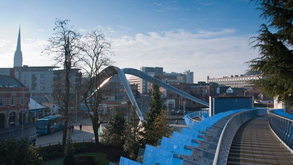 Coventry skyline with Whittle Arch on Millennium square and the cathedral, seen from the glass bridge