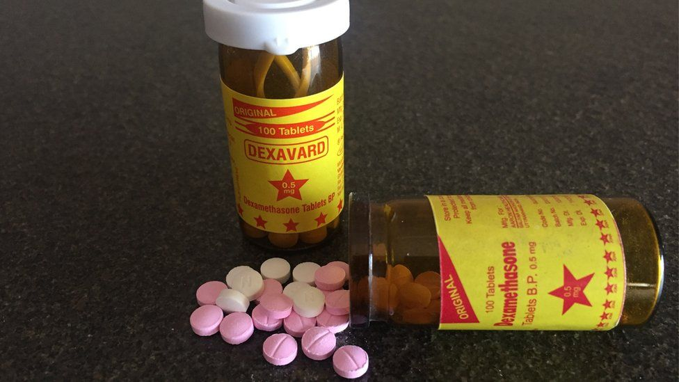 Two plastic bottles containing small pink and white pills.