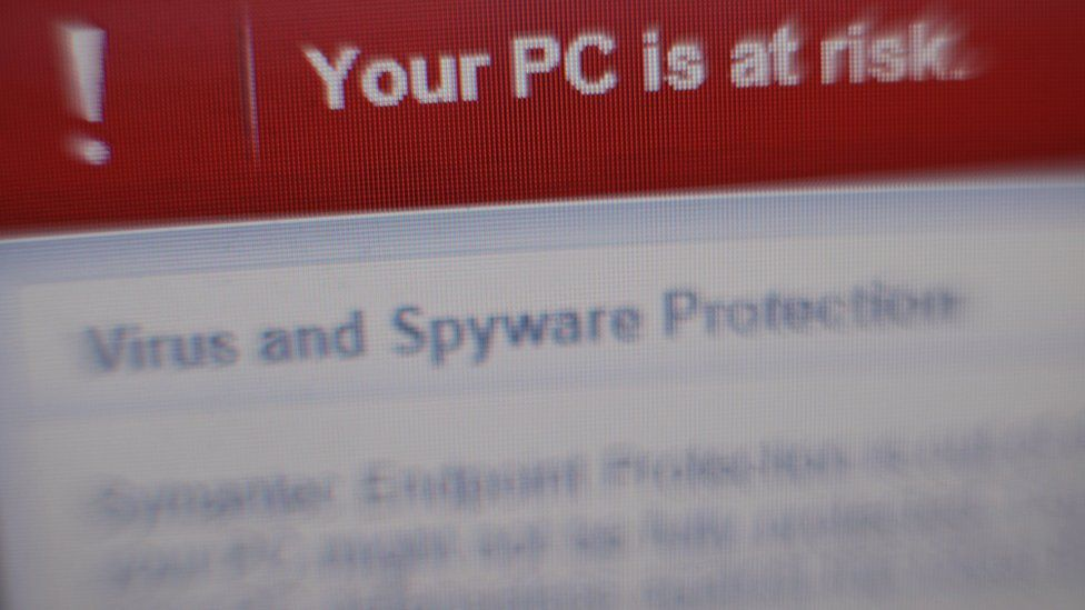 A virus and spyware warning message on a laptop screen