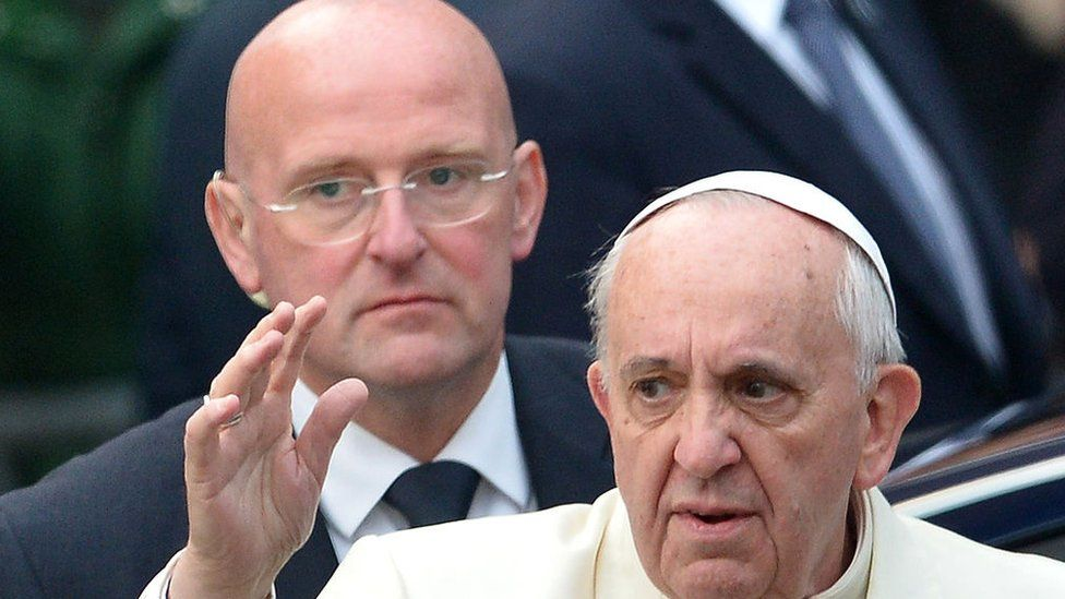 Pope Francis waving, with Domenico Giani behind him
