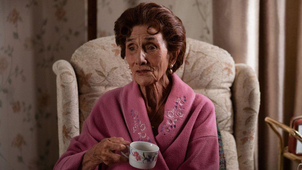 June Brown as Dot Branning in EastEnders, sitting in an armchair drinking a cup of tea