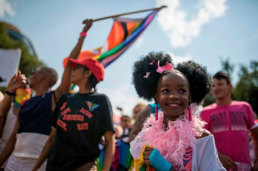 A young girl wearing a pink feather boa and matching earrings and hair bows takes part in the march.