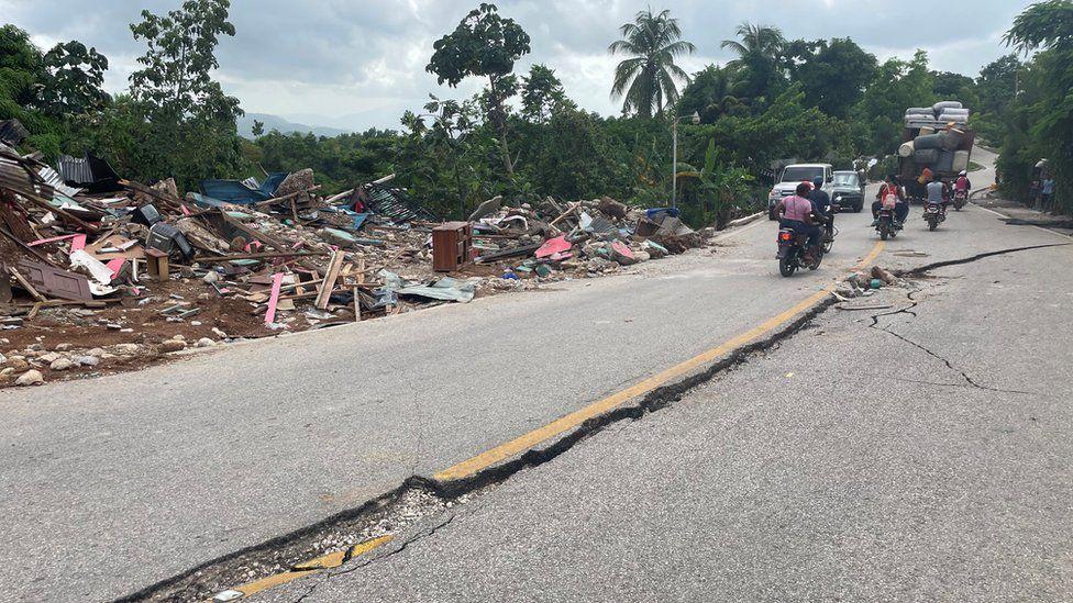 Motorists try to avoid cracks on a road in Marceline, Haiti