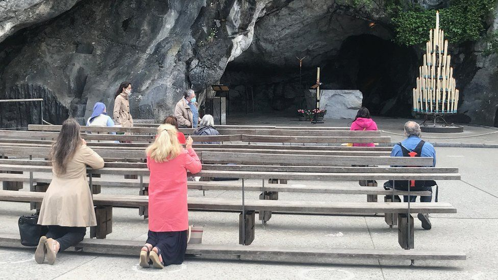 Worshippers pray at the grotte in Lourdes