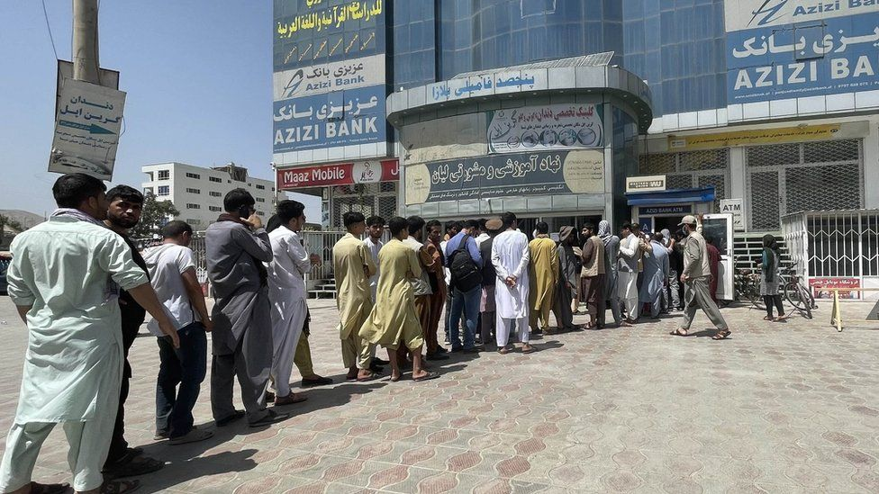 Afghan people line up outside AZIZI Bank to take out cash as the Bank suffers amid money crises in Kabul, Afghanistan, on August 15, 2021.
