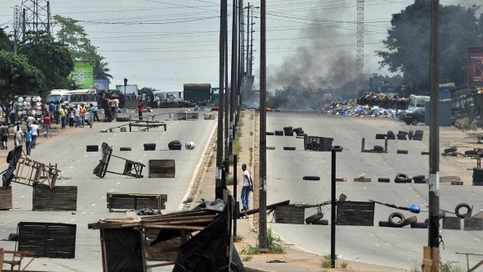 Residents walk past barricades and burning tires on the main road leading to the Abobo district of Abidjan on March 15, 2011