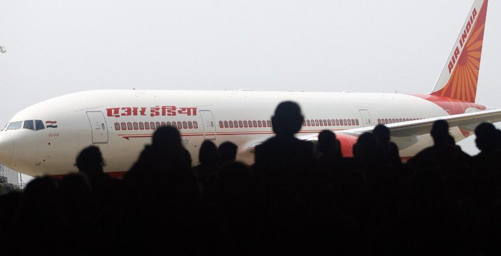 Air India employees look at the newly acquired Boeing 777-200 LR aircraft, 'ASSAM', as it stands on the tarmac of the Chattrapati Shivaji International airport in Mumbai, 30 July 2007, on the eve of Air India?s inaugural non-stop operations in the Mumbai-New York sector. I
