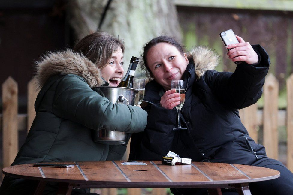 Women take a selfie with their drinks