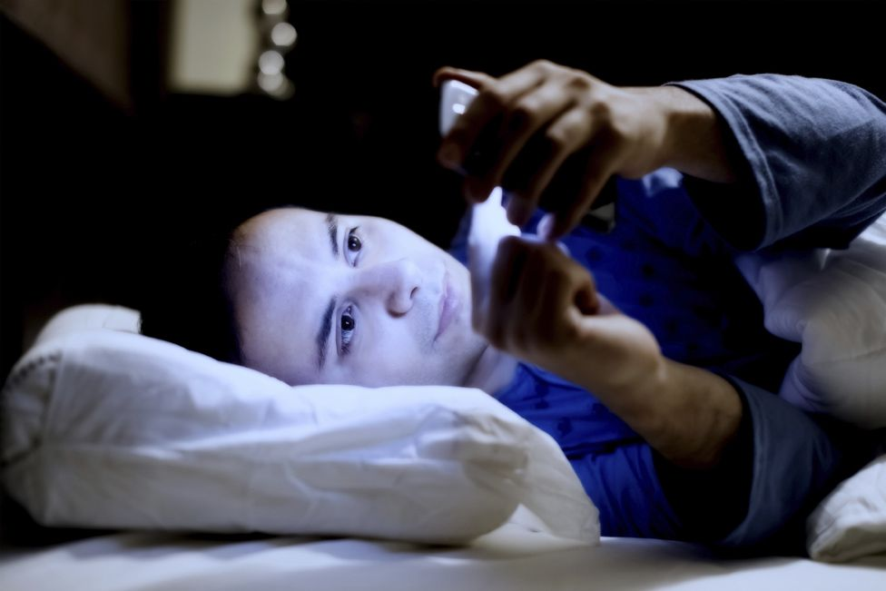 Man in bed on email